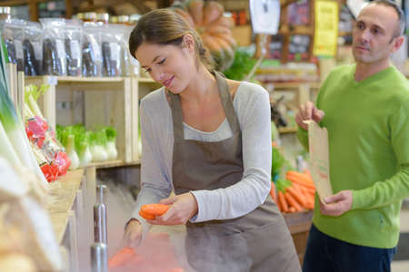 Shop assistant serving carrots to customer Stock Photo