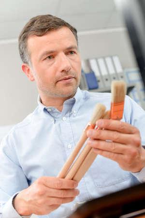 Man holding selection of paintbrushes Stock Photo