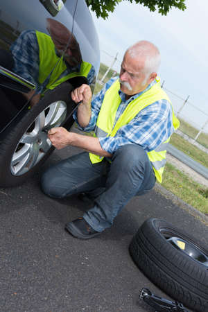 superannuated: aged man changing leaking tire on the verge