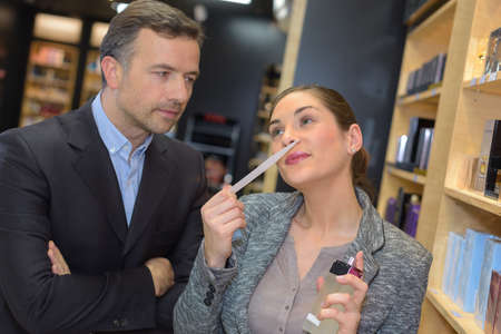 spendthrift: Lady smelling perfume, man looking on with serious expression