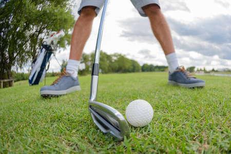 poised: Man poised to strike golfball