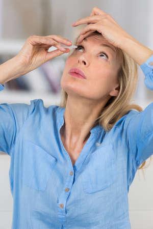 a woman putting eye drops in her eyes Reklamní fotografie - 73346000