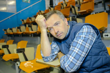 Man in auditorium looking fed up