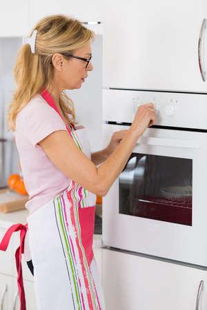 mandil: Madre del ama de casa que fija el horno para cocinar la comida