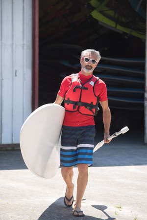 lifevest: man holding stand up paddle board walking towards the water Stock Photo
