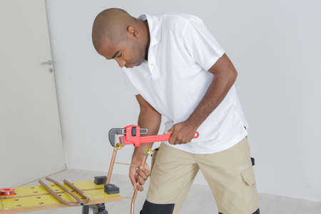 Man using wrench on copper pipe