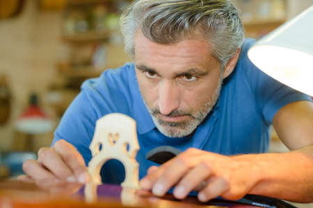 skilled: luthier installing a bridge Stock Photo