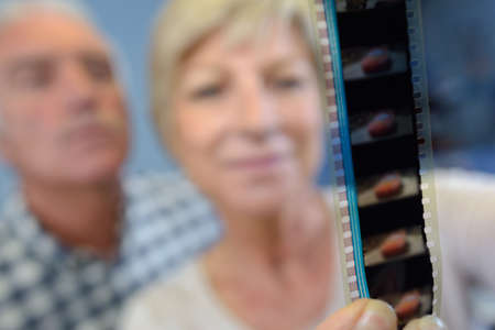 negatives: Senior couple looking at film strip negatives Stock Photo