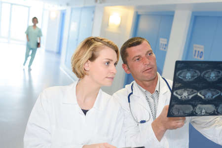 Medical staff looking at xrays in hospital corridor Stock Photo