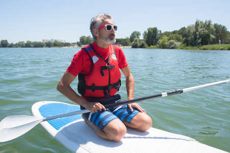 mature attractive rider contemplating nature sitting on paddle board Stock Photo