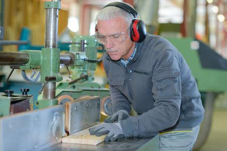 Senior carpenter using machinery Stock Photo