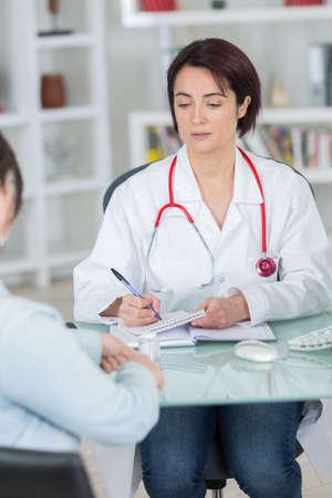 writing prescription after diagnosing sick patient Stock Photo