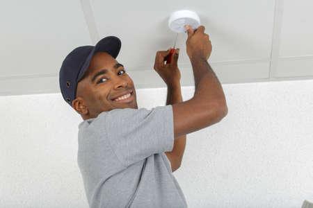 Hombre que encaja el detector de humo Foto de archivo - 73398020