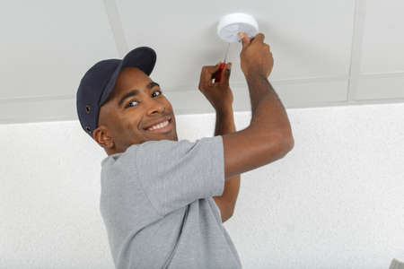 Man fitting smoke detector