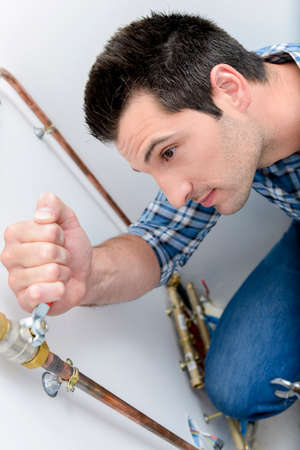 Plumber making adjustments to the heating system