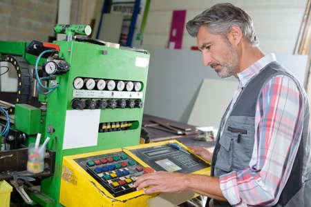 worker adjusting the machines program Reklamní fotografie