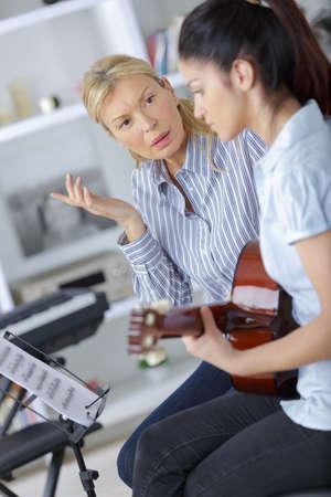 admonish: Music teacher reprimanding guitarist