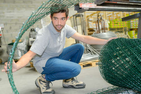 Man opening roll of fencing wire Stock Photo