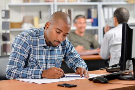 amend: Man sat at desk working on blueprints Stock Photo
