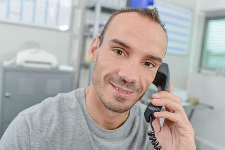 communication occupation: Young man on telephone, smiling