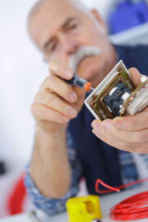jumpsuite: senior electrician is checking an outlet