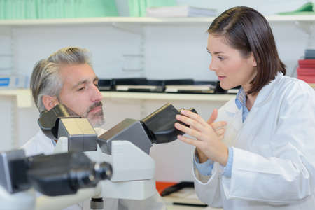 eyepiece: Laboratory technician in discussion with colleague