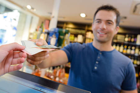 man paying for purchase in wine merchant Stock Photo