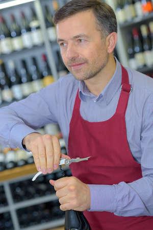 trad: Shopkeeper opening bottle of wine