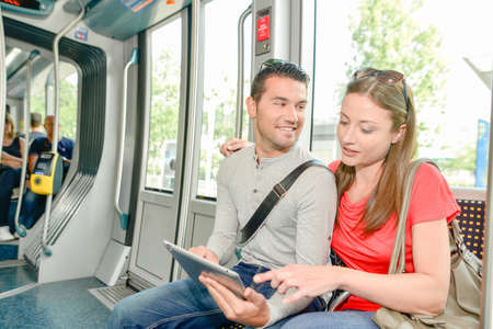 railway transportations: Couple on public transport, looking at tablet Stock Photo