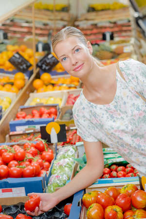 grocers: Young woman buying tomatoes