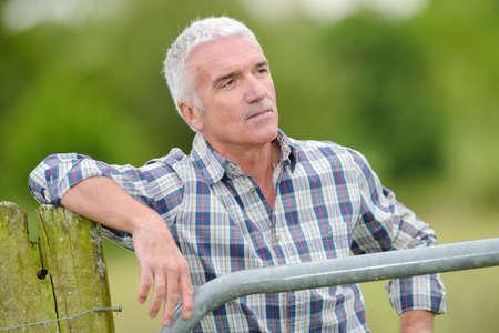 outdoorsman: outdoorsman leaning on fence Stock Photo