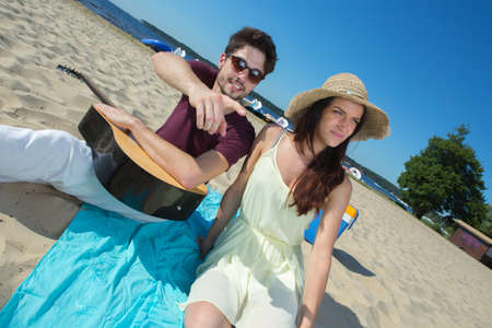 young man with his guitar and girlfriend on the beach