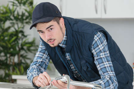 watertap: young craftsman repairing tap in a kitchen