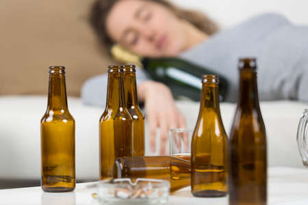 girl in depression drinking alcohol in solitude Stock Photo