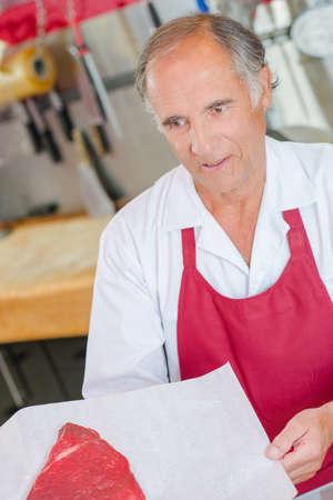 Butcher holding steak on parchment paper