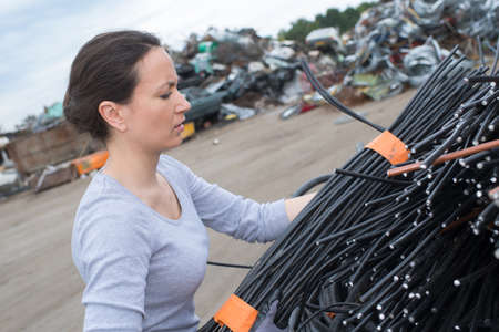 salvage yards: Woman lifting bundle of cables Stock Photo