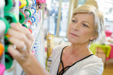 Woman choosing reel of ribbon