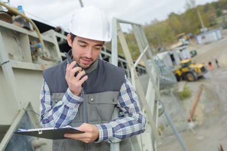 communication industry: Man on construction site talking into walkie talkie Stock Photo
