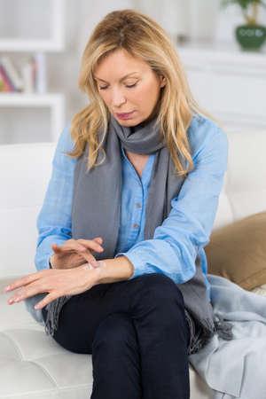 handcarves: senior attractive woman spread cream on her forearm