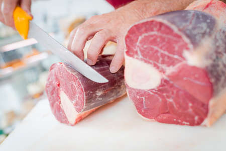 Butcher slicing meat Stock Photo