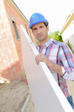 Builder carrying plank of wood Standard-Bild