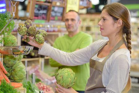 salesgirl: salesgirl with artichokes Stock Photo