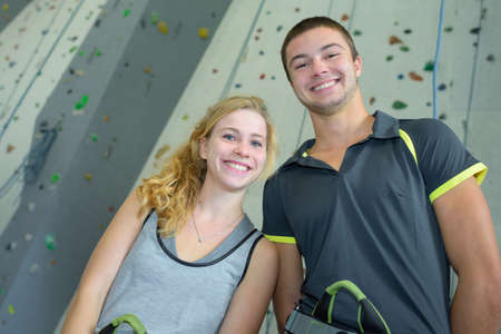 Portrait of young people in front of climbing wall Stock Photo
