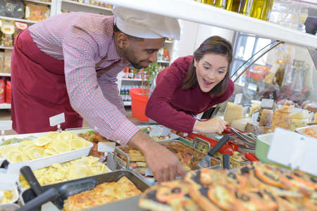 shopkeeper: shopkeeper gives pastry to woman