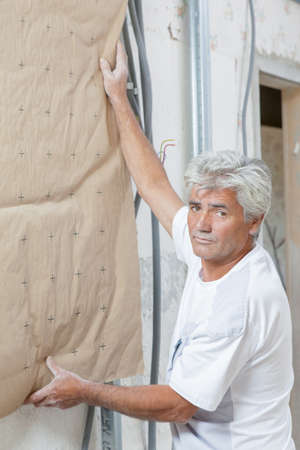rockwool: Man holding insulation against wall