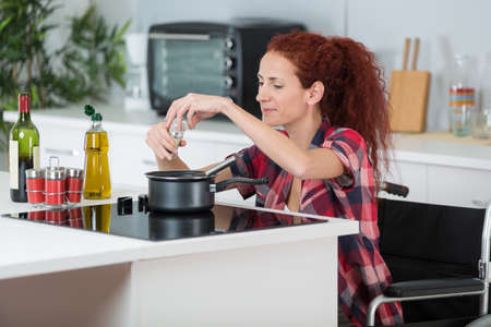 adjusted: disabled woman cooking in her kitchen Stock Photo