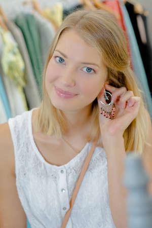 alkalmasság: Lady gazdaság fülbevaló a fülébe Stock fotó