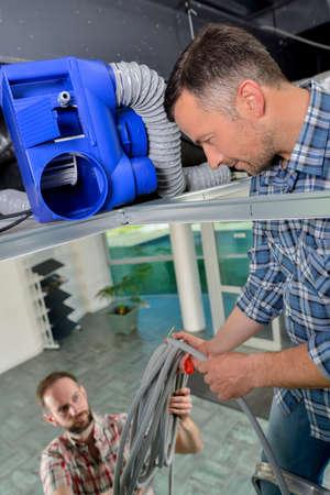 heat register: Team repairing ventilation system Stock Photo