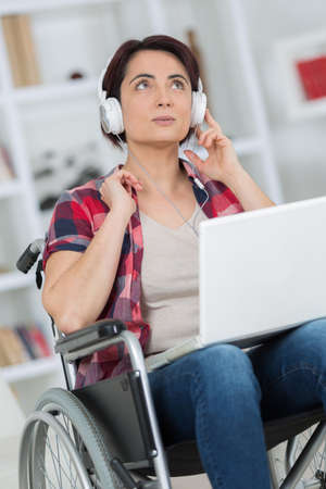 paraplegico: woman in a wheelchair enjoys music in headphones