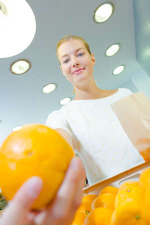 grocers: Closeup of orange, lady holding paper bag in background Stock Photo
